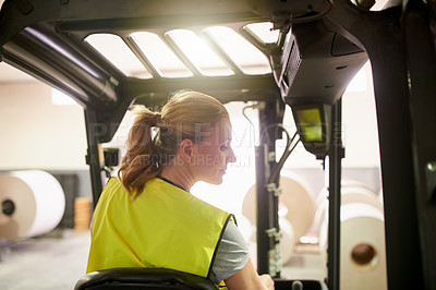 Buy stock photo Shot of a mature woman driving a forklift in a factory