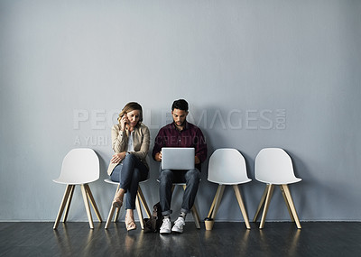 Buy stock photo Full length shot of two young businesspeople using their technology while sitting together against a gray studio background