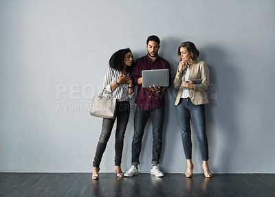 Buy stock photo Full length shot of three young businesspeople using their technology while standing against a gray background in the studio