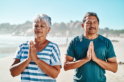 Buy stock photo Cropped shot of a focused senior couple standing with their palms together in meditation on the beach during the day