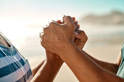 Buy stock photo Cropped shot of an unrecognizable senior couple holding hands on the beach during the day