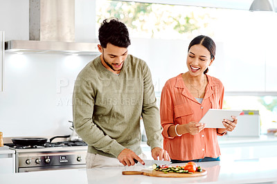 Buy stock photo Shot of a couple using a digital tablet while preparing a meal
