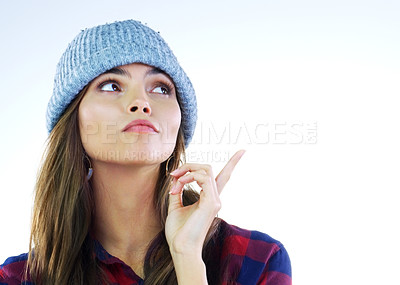 Buy stock photo Cropped shot of a young woman pointing at something against a white background
