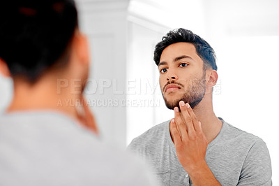 Buy stock photo Shot of a handsome young man looking at his face in the mirror at home
