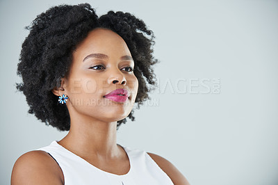 Buy stock photo Cropped studio shot of an attractive young woman standing and looking away while posing against a gray background