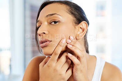 Buy stock photo Cropped shot of an attractive young woman squeezing a pimple on her face in front of the bathroom mirror at home