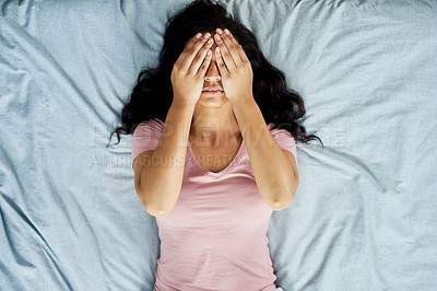 Buy stock photo High angle shot of an attractive young woman holding her eyes closed while lying on top of her bed at home