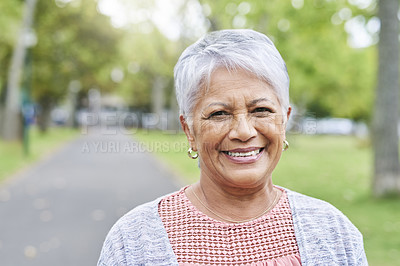 Buy stock photo Cropped portrait of a retired senior woman standing and smiling in the park alone during the day