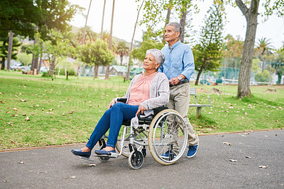 Buy stock photo Full length shot of a senior man pushing his content senior wife in a wheelchair in the park