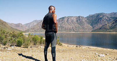 Buy stock photo Shot of a sporty young man admiring the scenic view while out for a run