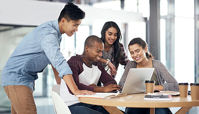 Buy stock photo Shot of a group of young men and women using a laptop while studying together at college