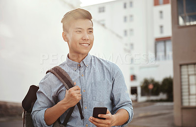 Buy stock photo Shot of a happy young student using his smartphone in the city