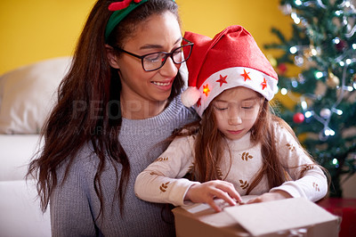 Buy stock photo Shot of a young woman celebrating Christmas with her daughter at home