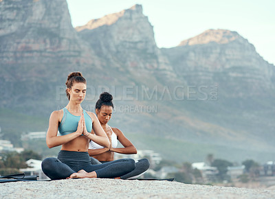Buy stock photo Shot of two sporty young woman practicing yoga together outdoors