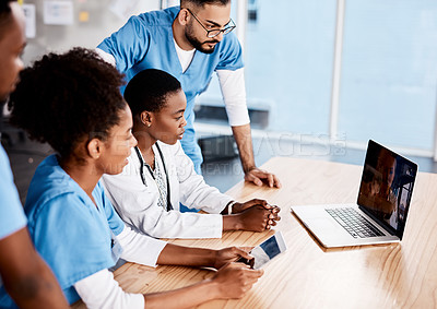 Buy stock photo Shot of a group of young doctors having a video conference with a laptop in a hospital
