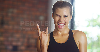 Buy stock photo Shot of a young woman doing the rock on hand sign while working out at the gym
