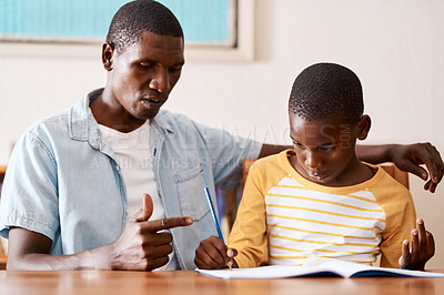 Buy stock photo Cropped shot of a man helping his son with his homework