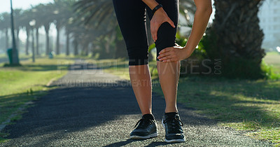Buy stock photo Cropped shot of an unrecognizable woman suffering from a knee injury while out running