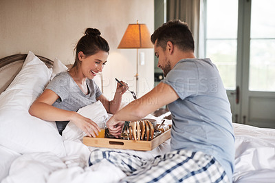 Buy stock photo Shot of an affectionate young couple enjoying breakfast in bed together in their bedroom at home