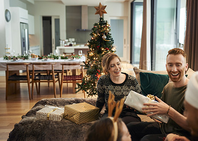 Buy stock photo Shot of young friends opening their Christmas gifts together at home