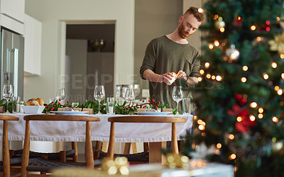 Buy stock photo Shot of a young man setting a table for a Christmas party at home