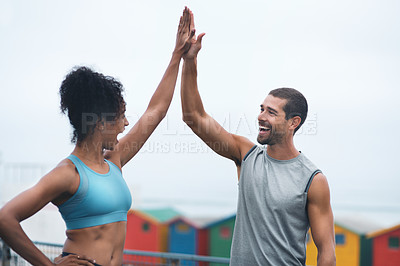 Buy stock photo Shot of two sporty young people giving each other a high five while exercising outdoors