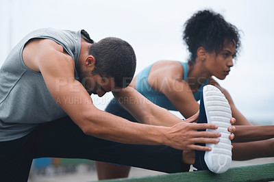 Buy stock photo Shot of two sporty young people stretching while exercising outdoors