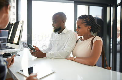Buy stock photo Shot of a happy young couple using a cellphone while checking in at the reception of a hotel