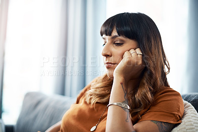 Buy stock photo Cropped shot of a young woman sitting at home