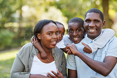 Buy stock photo Portrait of a cheerful young family holding each other in their arms while standing inside of a park outside during the day