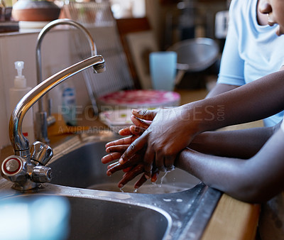 Buy stock photo Cropped shot of an unrecognizable young boy and his mother washing hands together in the kitchen at home