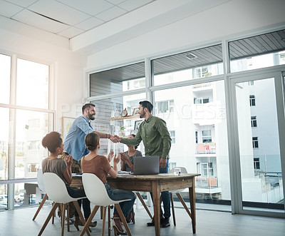 Buy stock photo Shot of young businessmen shaking hands during a meeting in a modern office