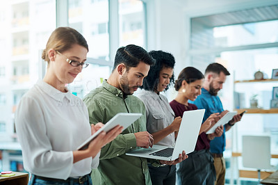 Buy stock photo Shot of a group of businesspeople using digital devices while standing in line in an office