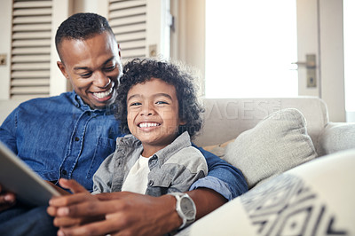 Buy stock photo Shot of a young boy holding a digital tablet while sitting at home with his father