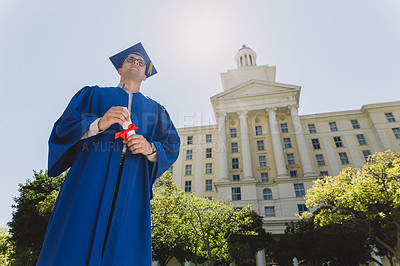 Buy stock photo Shot of a confident young man holding his diploma on graduation day