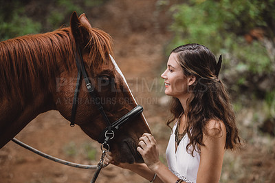 Buy stock photo Shot of a young woman bonding with her horse in nature