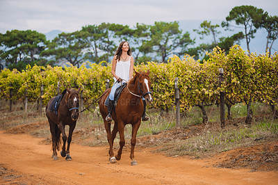 Buy stock photo Shot of a young woman riding a horse on a farm with another walking beside them