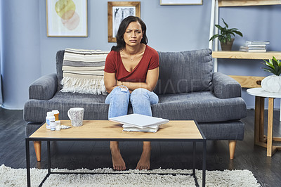 Buy stock photo Full length shot of an attractive young woman suffering from stomach cramps while sitting on her couch at home