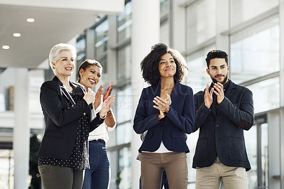 Buy stock photo Cropped shot of a diverse group of businesspeople standing together and clapping while in the office during the day