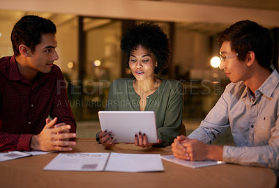 Buy stock photo Cropped shot of a group of young businesspeople using a digital tablet while working late in a modern office