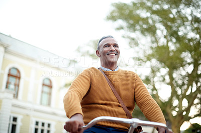 Buy stock photo Shot of a mature businessman riding a bicycle through the city