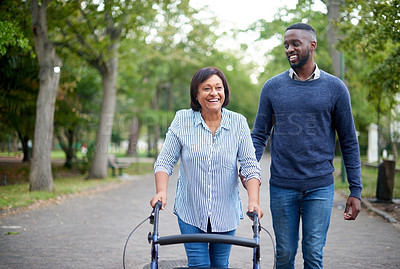Buy stock photo Cropped shot of a happy mature woman using a walker while a handsome young man assists her in the park