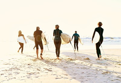 Buy stock photo Full length shot of a group of unrecognizable senior people holding their surfboards and walking towards the sea to surf