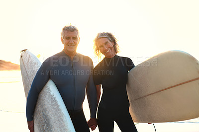 Buy stock photo Cropped portrait of a happy senior couple carrying their surfboards while walking along the beach at sunset