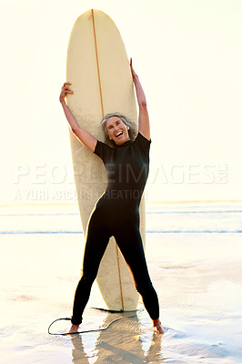 Buy stock photo Full length portrait of a happy senior woman standing and posing with her surfboard while on the beach