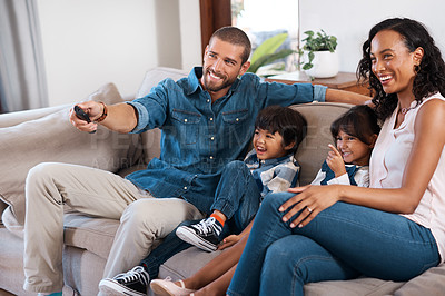 Buy stock photo Shot of a couple watching something on the television with their two young kids
