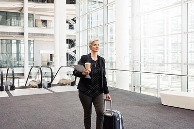 Buy stock photo Shot of a mature businesswoman walking through an airport