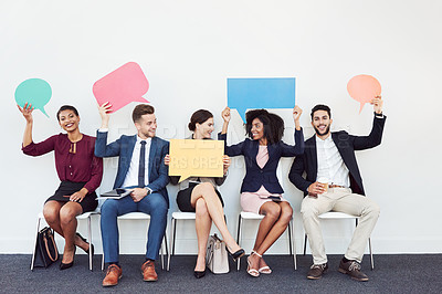 Buy stock photo Studio shot of a group of young businesspeople holding speech bubbles while sitting in a row against a white background