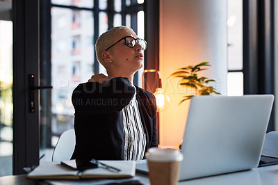 Buy stock photo Shot of an attractive young businesswoman feeling discomfort on her neck while working late in her office