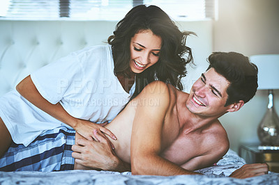 Buy stock photo Shot of an affectionate young couple spending quality time together in their bedroom at home